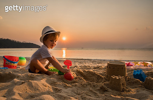 Little boy sitting in sand at the beach and playing with his toys at sunset. Copy space. - gettyimageskorea