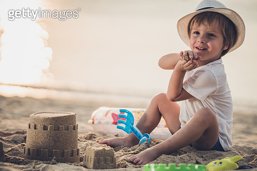 Smiling little boy playing with toys in sand on the beach. - gettyimageskorea