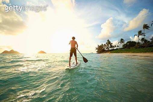 Caucasian man on paddle board in ocean - gettyimageskorea
