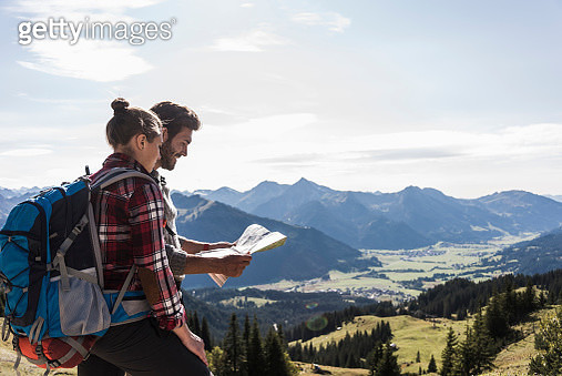 Austria, Tyrol, young couple looking at map in mountainscape - gettyimageskorea