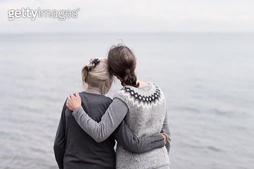 two generations women embracing, looking at sea - gettyimageskorea