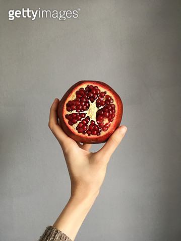 Womans hand holding a pomegranate - gettyimageskorea