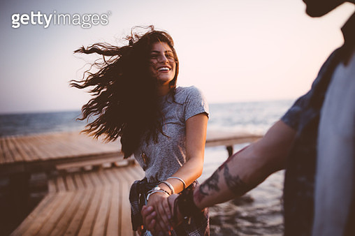 Young playful hipster couple holding hands on jetty at sunset - gettyimageskorea