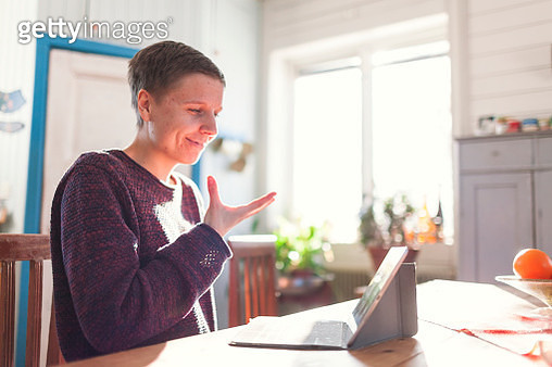 Woman having sign language conversation via video call on computer - gettyimageskorea