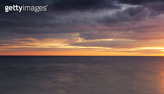Scenic View Of Sea Against Dramatic Sky During Sunset - gettyimageskorea