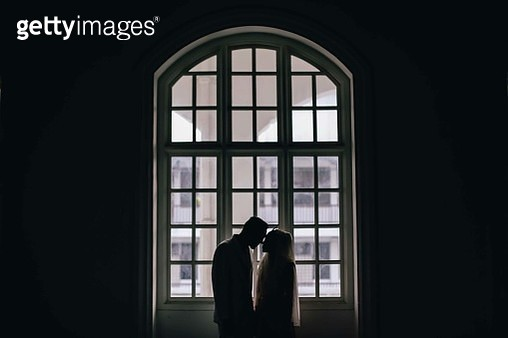Silhouette Couple Standing By Window In Building - gettyimageskorea