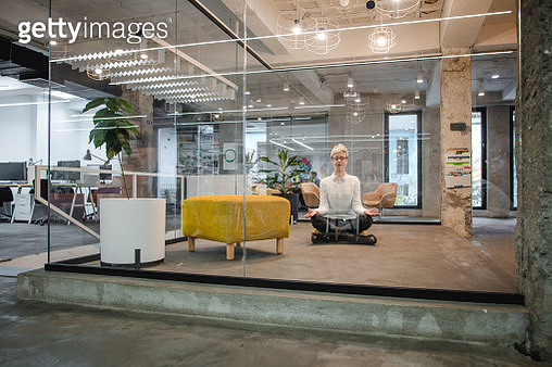Young relaxed female entrepreneur exercising Yoga in the office. - gettyimageskorea