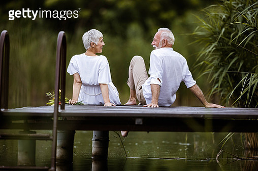 Back view of happy mature couple in white clothing communicating on a pier at lake. - gettyimageskorea