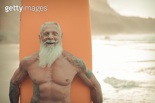 Senior man with orange longboard. Happy old guy having fun doing extreme sport. Joyful elderly concept - Image - gettyimageskorea