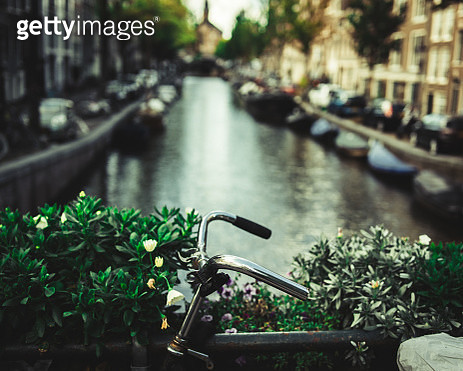 Close-Up Of Bicycle On Railing Over Canal In City - gettyimageskorea