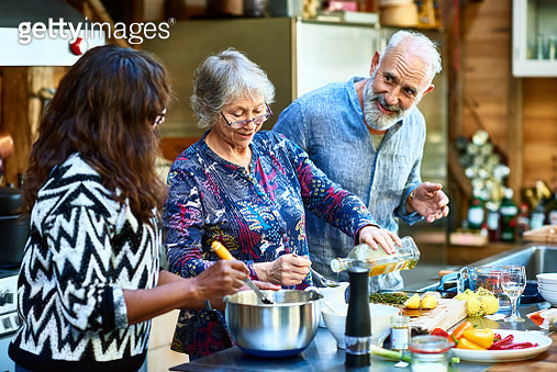 Woman wearing glasses pouring oil and making food, mature man with beard talking to female friend, working as a team, three people cooking at home - gettyimageskorea