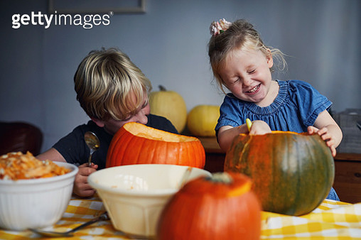 Brother and sister having fun laughing while scooping out pumpkins ready for carving - gettyimageskorea
