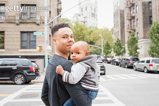 Young father walking with infant daughter in city neighborhood - gettyimageskorea