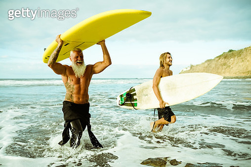 Best friends doing surfing in the summer time . People going out into the ocean. Sporty people lifestyle and extreme sport concept - Image - gettyimageskorea