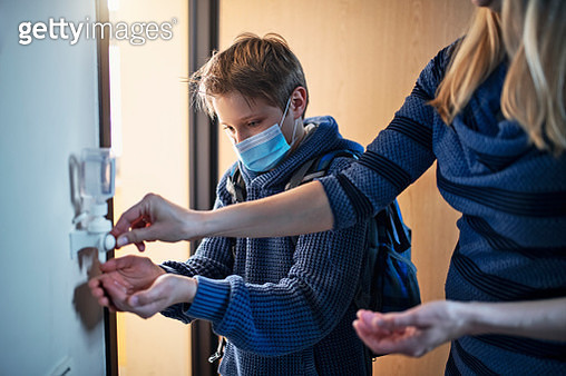 Little boy disinfecting hands after returning from school - gettyimageskorea
