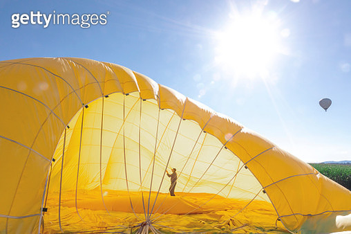 Man preparing the yellow envelope of a hot air balloon for take off - gettyimageskorea