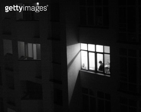 One window is lit in the darkness of the rest of the building. A man is standing thinking infront of it. - gettyimageskorea