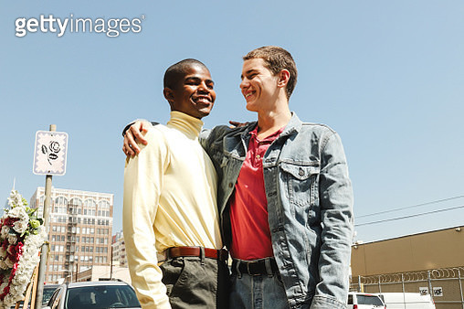 Two young males with their arms around each other and smiling during the day - gettyimageskorea