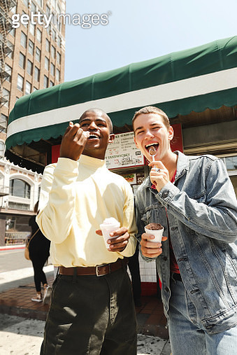 Two young males eating ice cream while standing outside of a coffee shop during the day - gettyimageskorea
