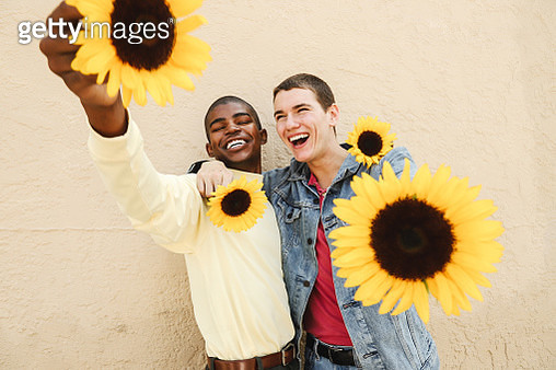Two young males being playful with their arms around each other and smiling while posing with sunflowers - gettyimageskorea