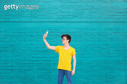 Young man taking a selfie with smartphone in front of blue brick wall - gettyimageskorea