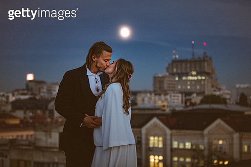 Affectionate bride and groom embraces and kisses on the rooftop at night - gettyimageskorea