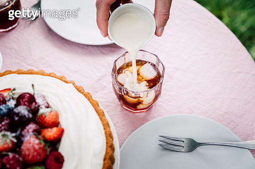 Hand of a woman adding milk in a cup of coffee on table. Woman preparing breakfast. - gettyimageskorea
