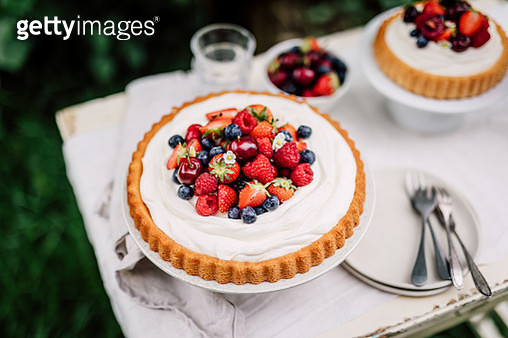 Homemade cake with cheese cream, fruits and berries on table outdoors in garden. Summer Sunday breakfast. - gettyimageskorea