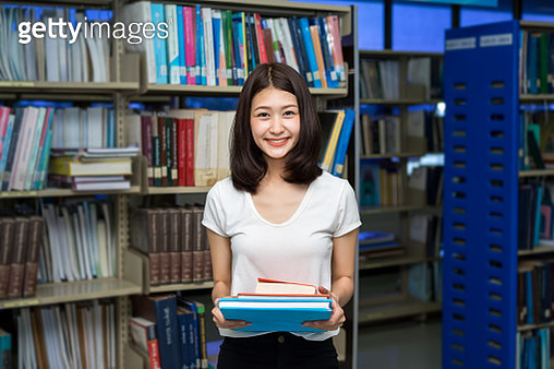 Portrait Of Young Woman Holding Books While Standing Against Shelves In Library - gettyimageskorea