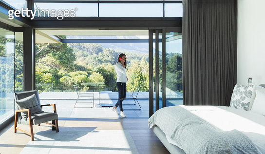 Woman talking on smart phone in patio doorway of modern, luxury bedroom - gettyimageskorea
