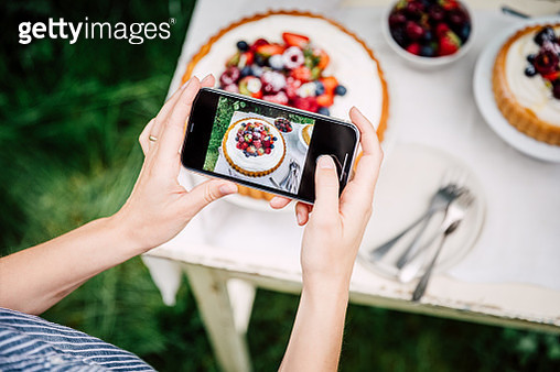 Point of view of a woman taking photos of fresh berries cake with her mobile phone. Female photographing freshly made fruit cake outdoors. - gettyimageskorea