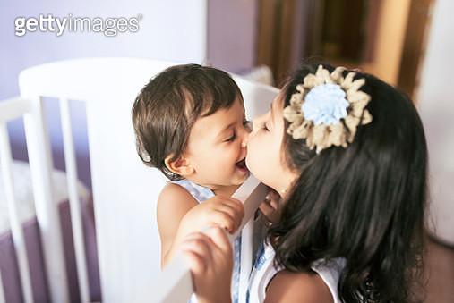 Sister kissing her little brother in bedroom - gettyimageskorea