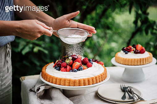 Close-up of a woman hands sifting powdered sugar on a cheesecake. Female preparing fresh fruits and berries cake outdoors in a garden. - gettyimageskorea