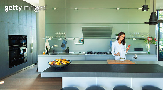 Woman with smart phone eating in modern kitchen - gettyimageskorea