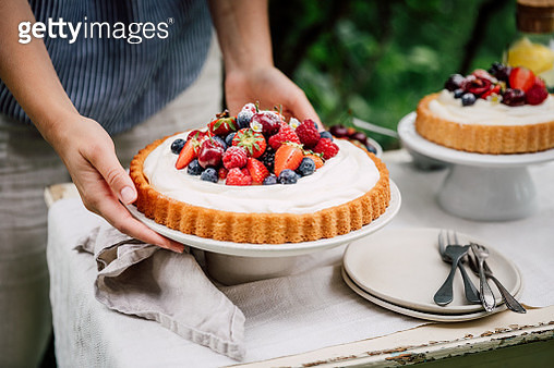 Close-up of a female placing homemade cheese cream and fruit cake on table. Woman setting up cake table outdoors in garden. - gettyimageskorea
