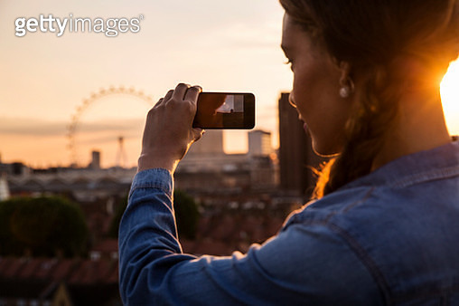 Young woman photographing skyline at sunset roof party in London, UK - gettyimageskorea