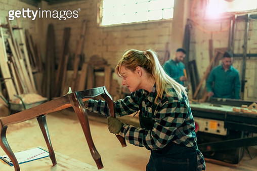 Portrait view of a female industrial worker in her 40s working as a carpenter in her workshop with sandpaper while her colleagues are in the background - gettyimageskorea