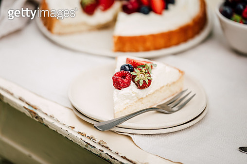 Close-up of a freshly made fruit cake slice served in a plate on a table. Homemade cheesecake with berries. - gettyimageskorea