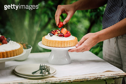 Close-up of a female preparing fruit cake for breakfast outdoors in garden. Woman decorating cheesecake with fresh berries. - gettyimageskorea