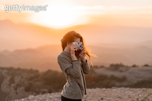 Spain, Barcelona, Natural Park of Sant Llorenc, woman taking a picture with vintage camera at sunset - gettyimageskorea