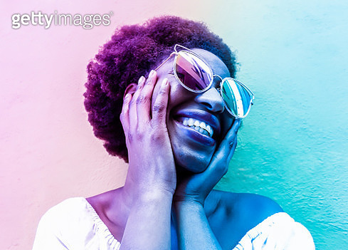 Close-Up Of Smiling Woman Wearing Sunglasses Against Wall - gettyimageskorea