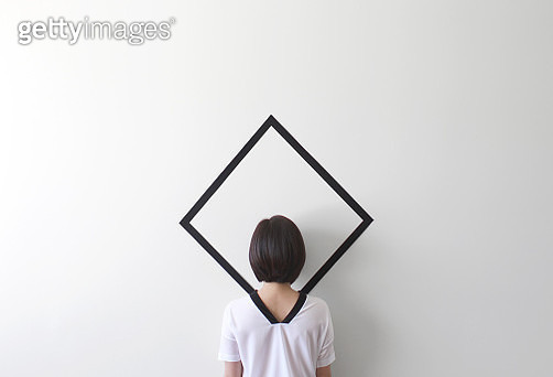 Conceptual woman camouflaged against a white wall - gettyimageskorea