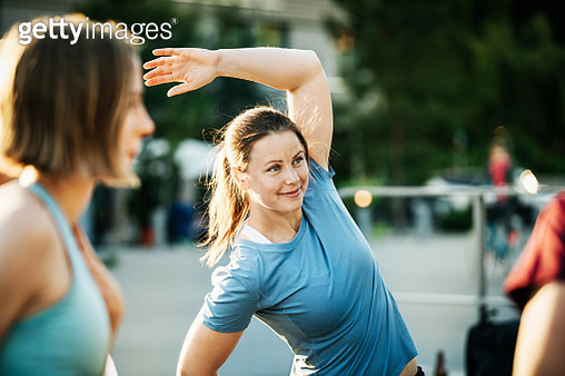 A group of women warming up outside together before going for a run through the city. - gettyimageskorea