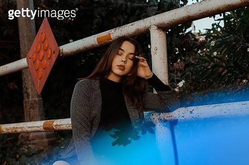 Young Woman Sitting By Metallic Railing - gettyimageskorea