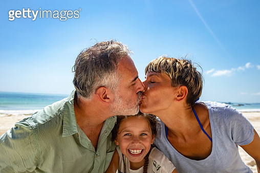 Mother and Father Kissing on Beach - gettyimageskorea