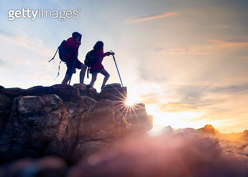 Young couple hikers climbing up hike on the peak of rocks mountain  during sunset - gettyimageskorea