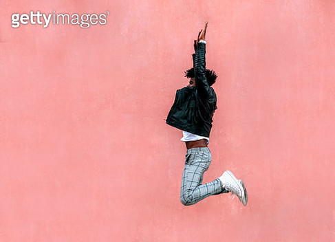 Mid adult man with arms raised jumping by pink wall in city - gettyimageskorea