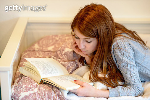 Redheaded teenage girl lying on bed reading a book - gettyimageskorea