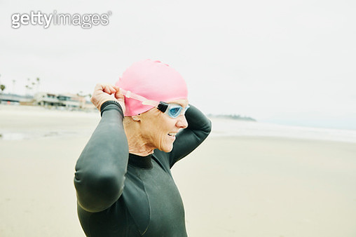 Mature woman standing on beach adjusting goggles before early morning open water swim - gettyimageskorea