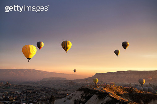 Beautiful sunrise over geology landscape of Cappadocia with hotter balloon and the take off site, a view from sunrise view point, Goreme ancient town. - gettyimageskorea